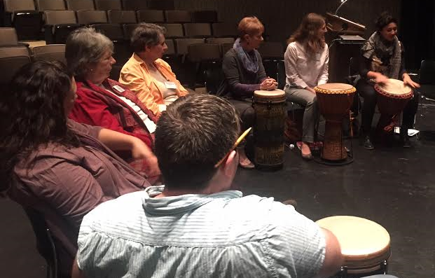 A group of 7 people participate in a drum circle as they learn about incorporating music into programs.