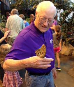 A man in a purple shirt is looking at a butterfly that has landed on his hand while other people are in the background.