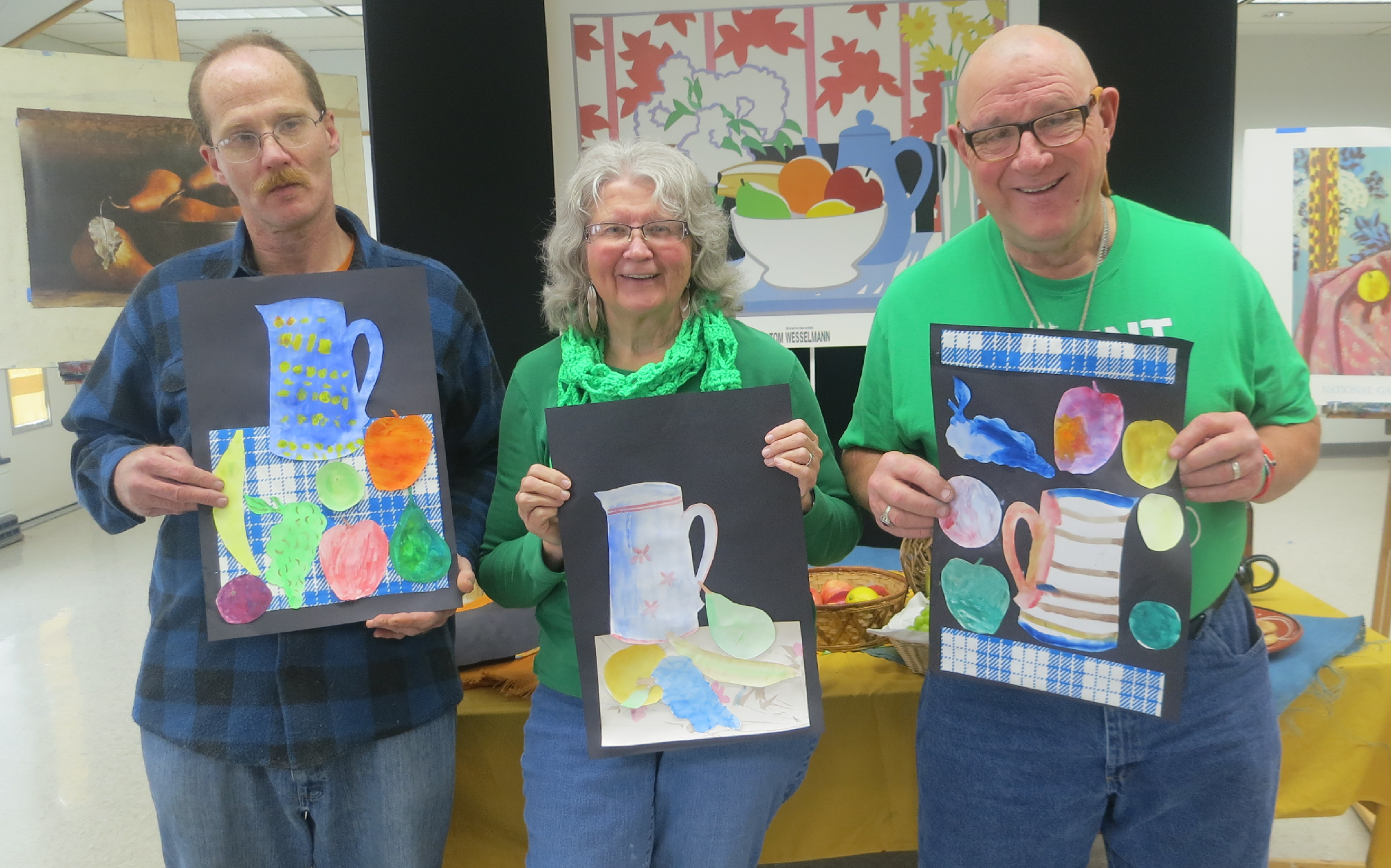 Three adults are holding up their paintings of a water pitcher and fruit.