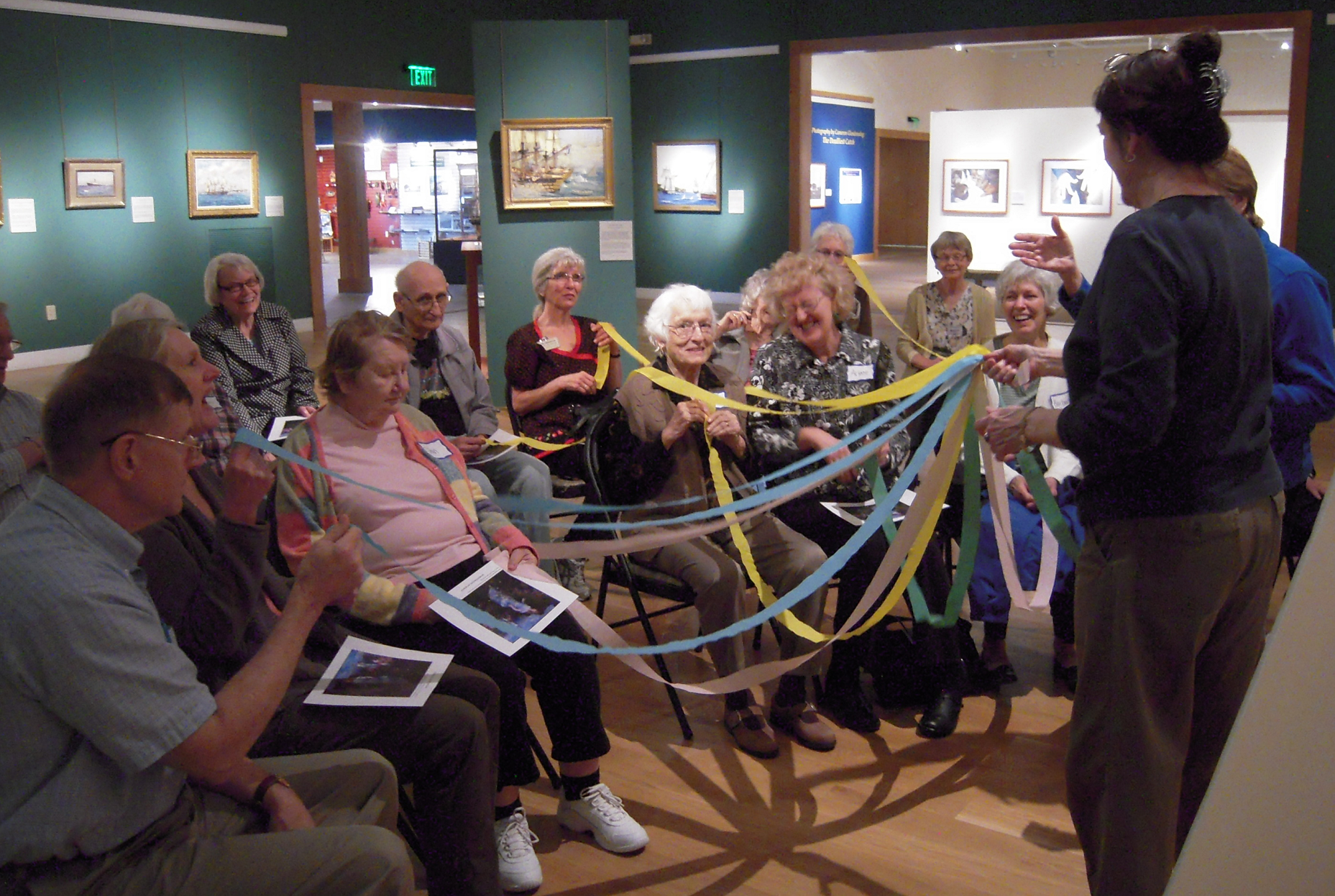 A group of 15 adults are holding colored streamers while seated in a gallery of paintings.