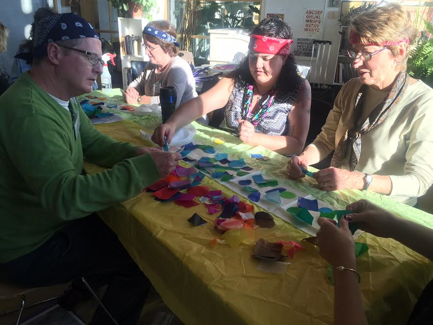 Four 2016 attendees work together on laying pieces of tissue paper on a silk scarf to create a colorful finished dyed scaft.